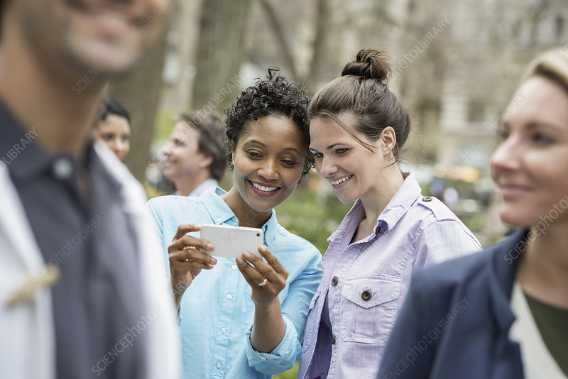 Two women sharing a smart phone