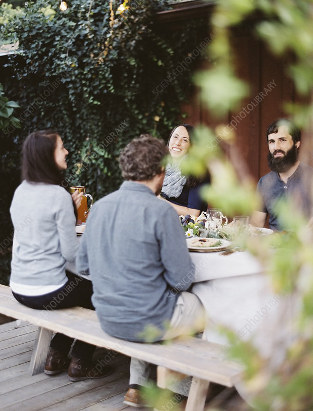 People around a table in a garden.
