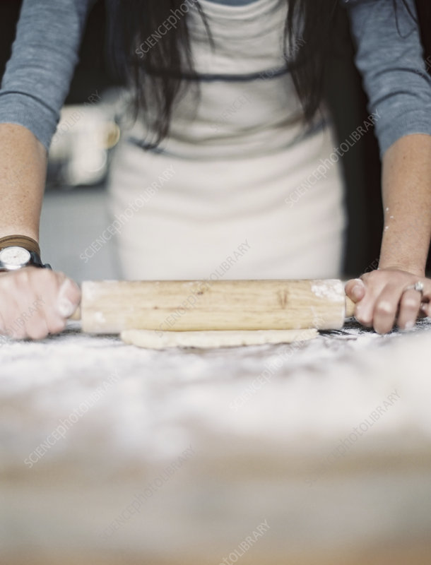 A woman rolling out pastry on table top