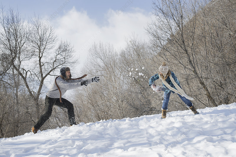 A couple having a snowball fight in snow