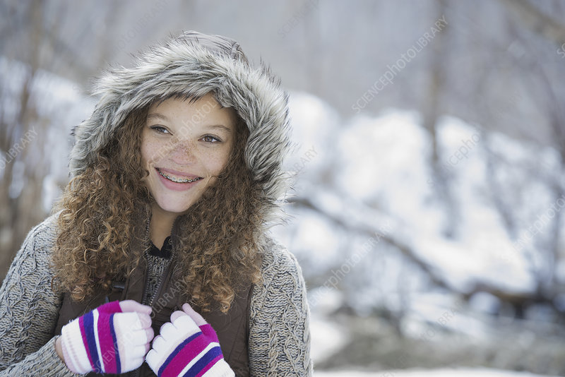 A young girl in a hat with ski gloves