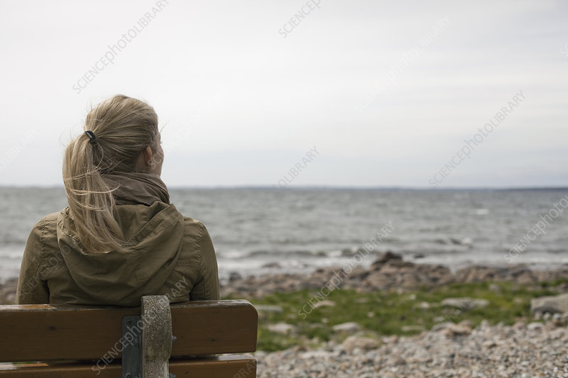 A woman on a bench looking out to sea.