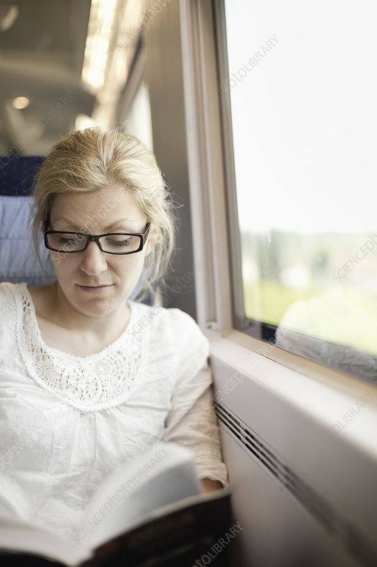 A woman reading a book on a train