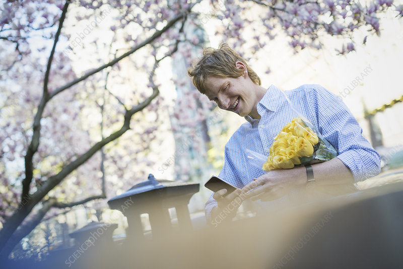 A man using a phone holding yellow roses
