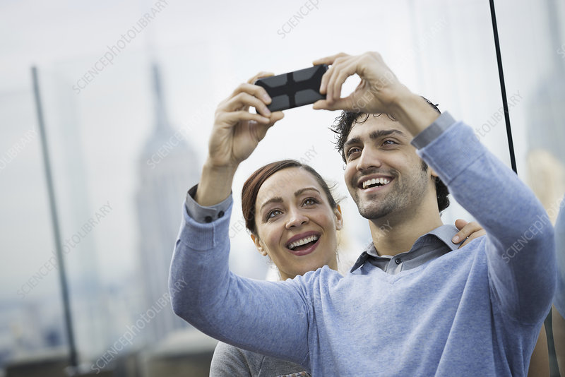 A young couple taking picture with phone