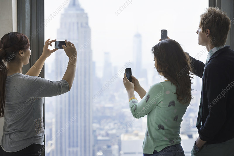 Three people taking pictures with phones