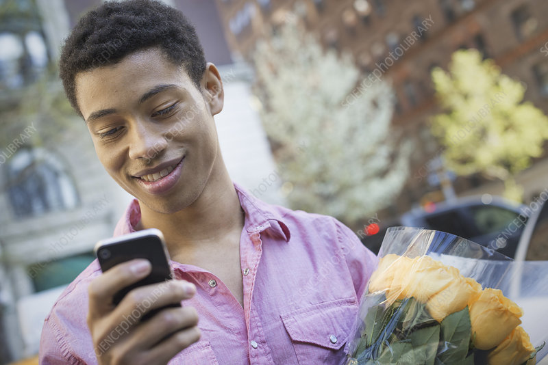 A young man holding a smart phone