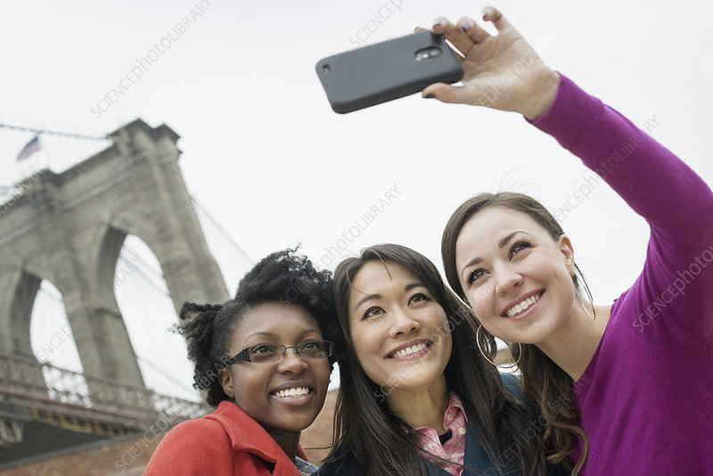 Three women, one taking a photograph.