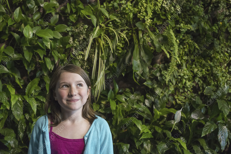 A girl in front of a wall of foliage