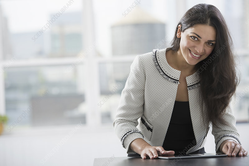 A woman at table using a digital tablet