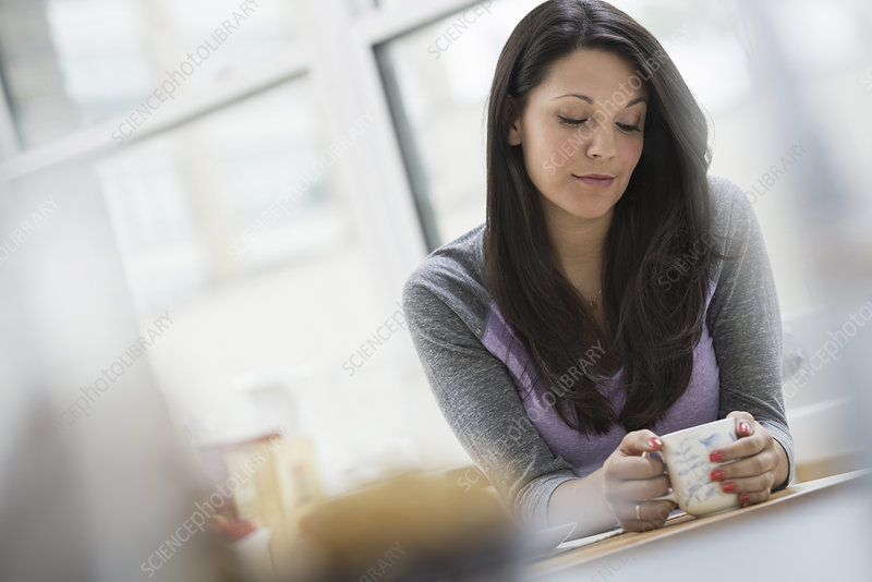 A young woman having a cup of coffee