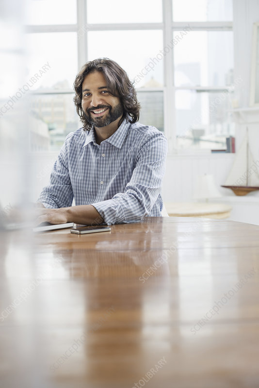A bearded man using a laptop computer.