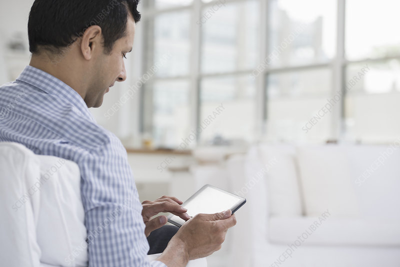 A man seated using a digital tablet