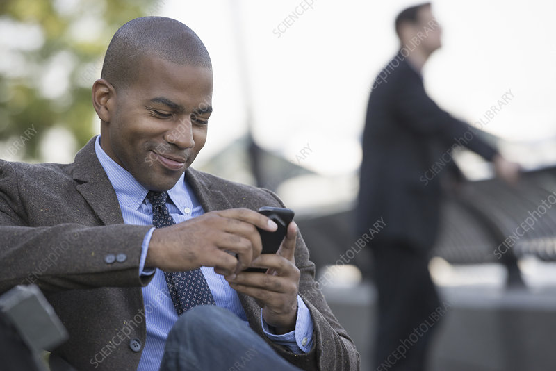A man seated using his smart phone
