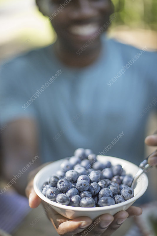 Man holding a bowl of fresh blueberries.