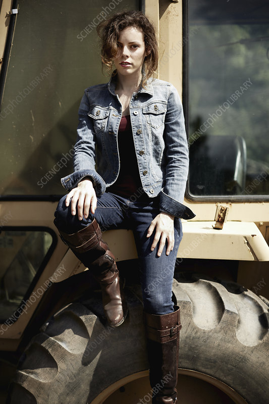 A young woman in denim jacket and boots