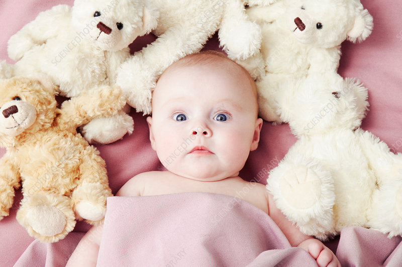 Baby girl lying surrounded by soft toys