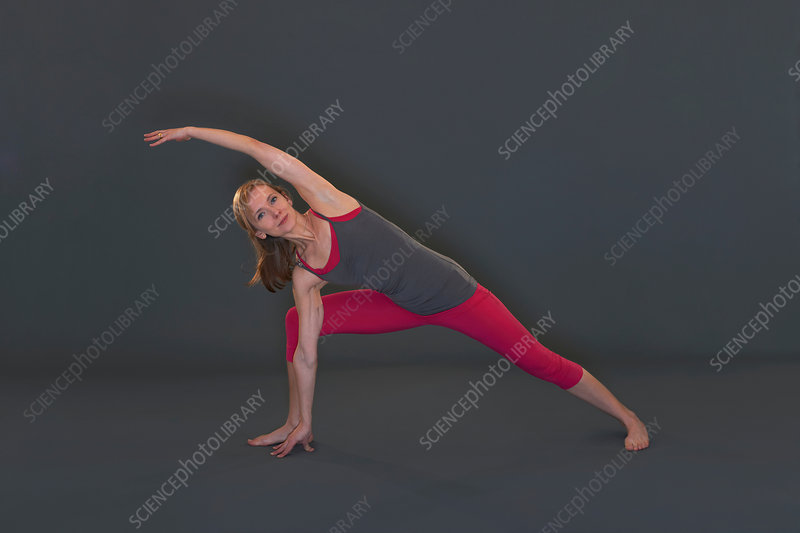 Woman in yoga pose on grey background