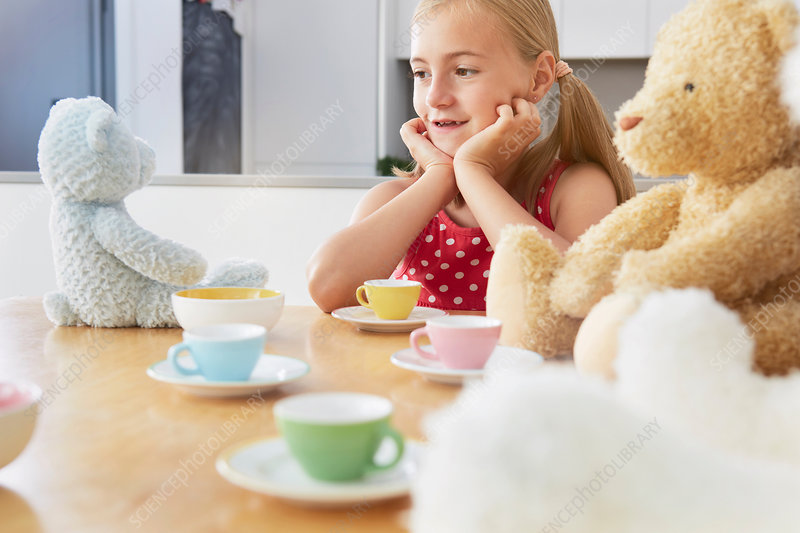 Girl having tea party with soft toys