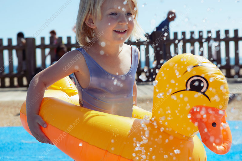 Child with duck-shaped float in pool
