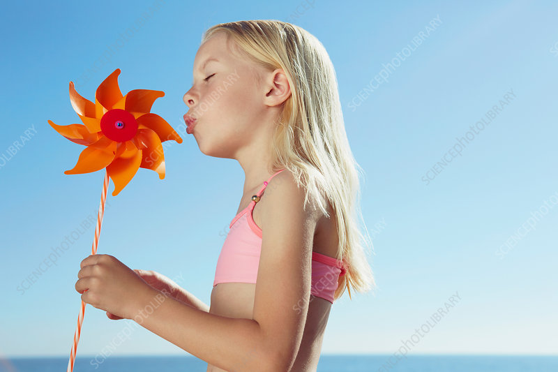 Girl blowing at toy windmill