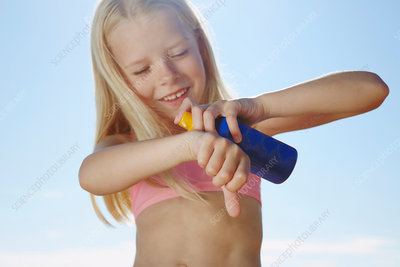 Girl spraying sunblock on hand