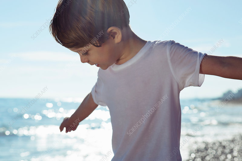Boy with arms outstretched on beach