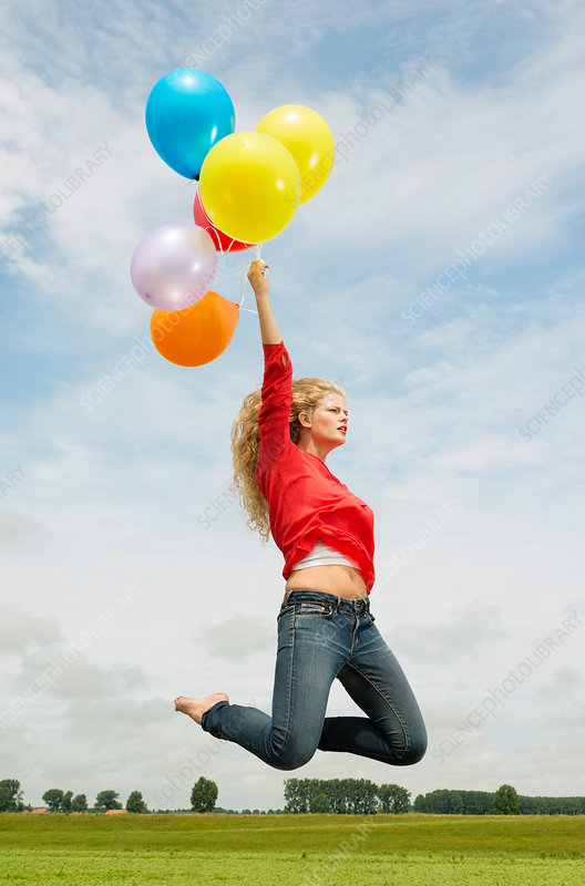 Woman jumping with balloons