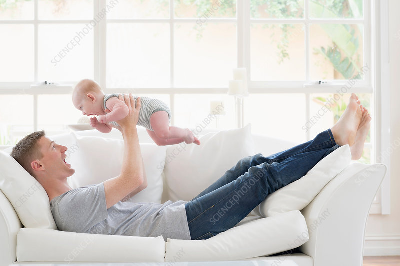 Father lying on sofa lifting baby