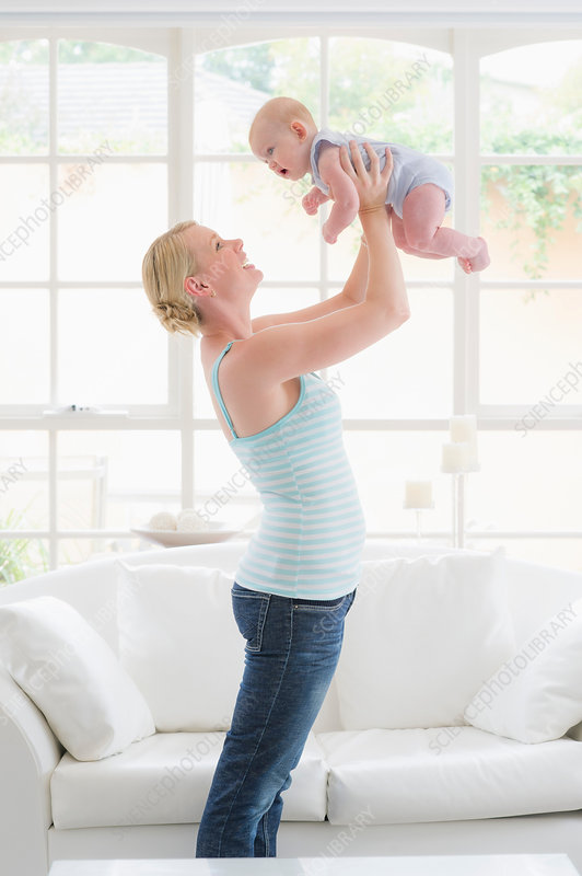 Mother standing holding up baby