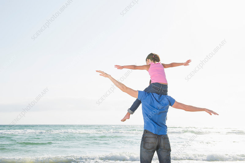 Girl sitting on father's shoulders