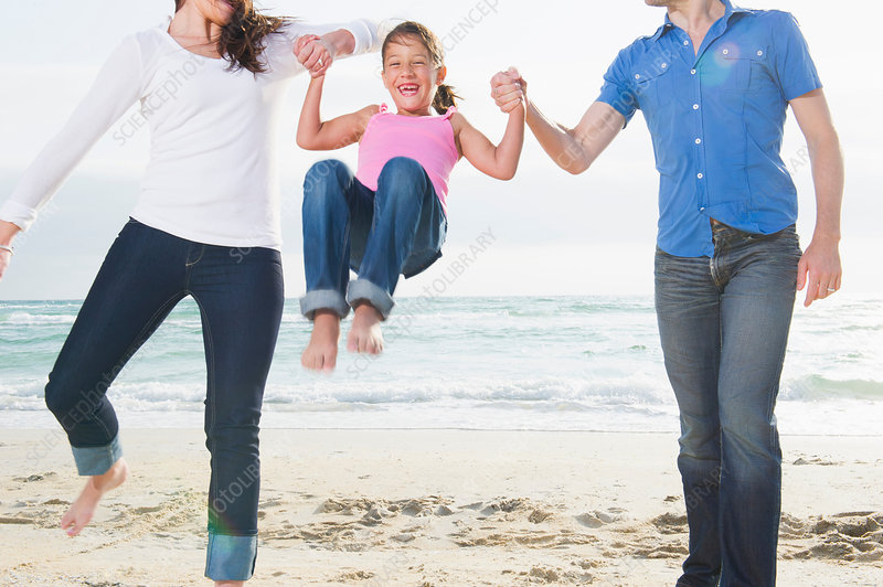 Mother and parents swinging girl on beach