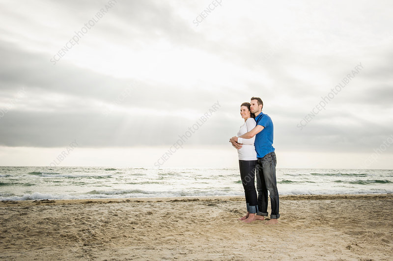 Young couple standing hugging on beach
