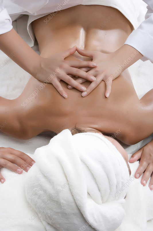 Masseuse pressing down on woman's back