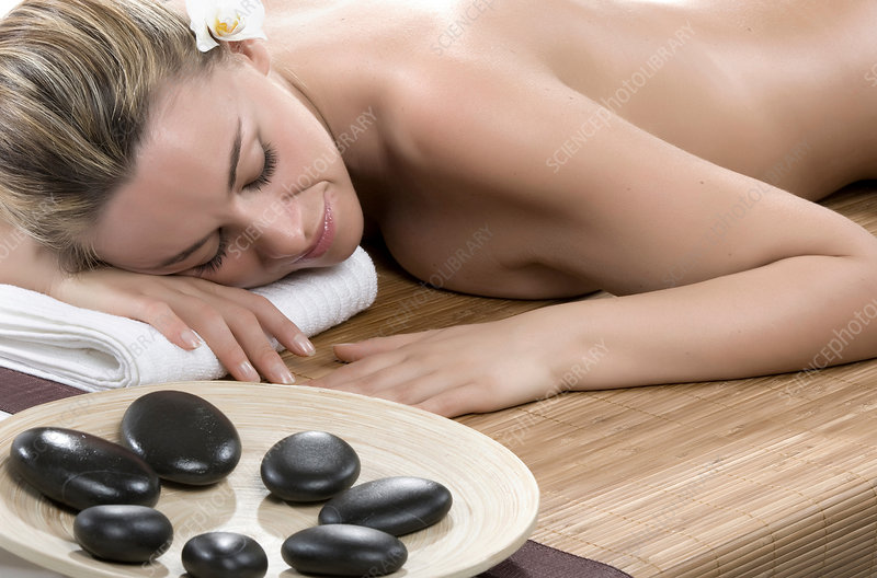 Woman having hot stone therapy