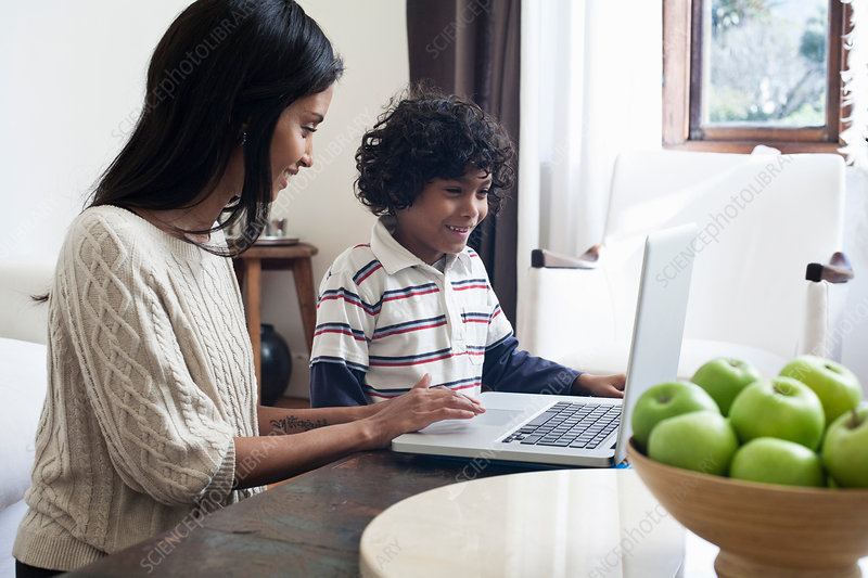 Mother and son using laptop