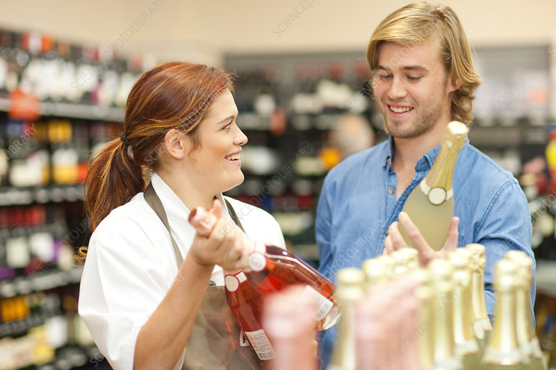 Shop assistant advising customer on wine