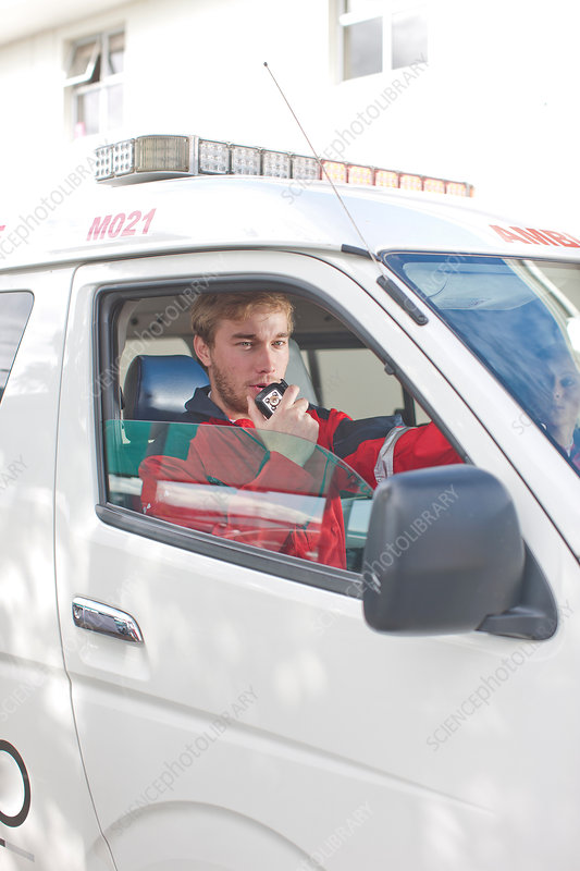 Paramedic in ambulance on walkie-talkie