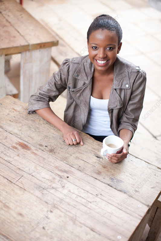 Woman holding coffee cup in street cafe