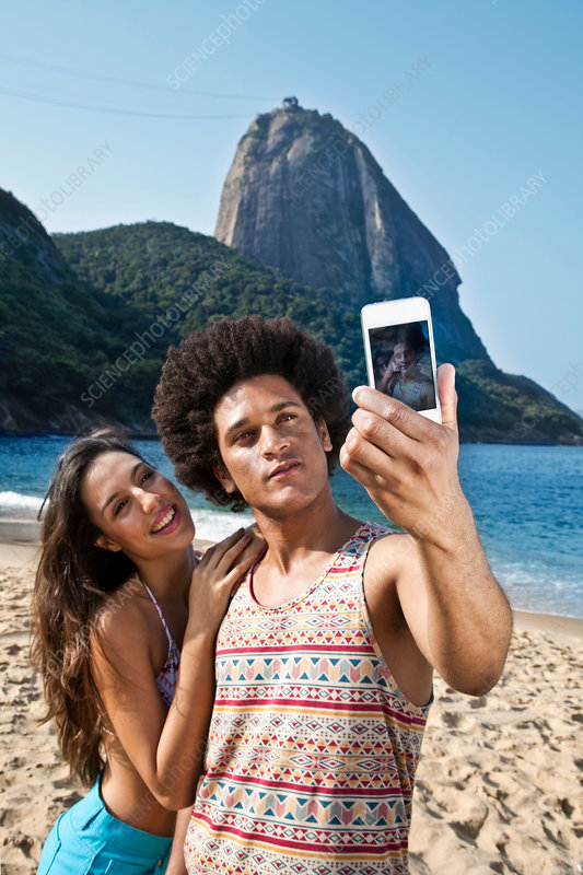 Couple photographing themselves on beach