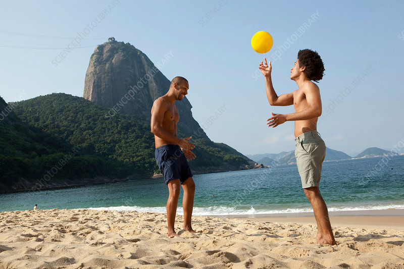 Two friends on beach with volleyball