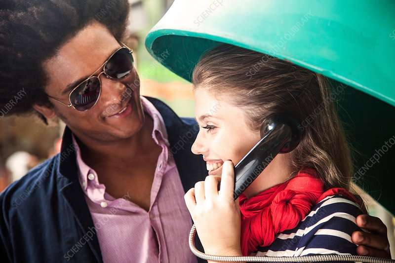 Young couple using pay telephone