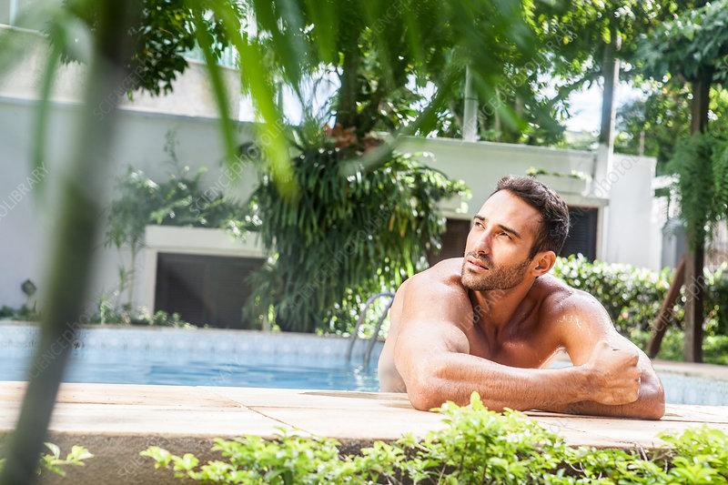 Man leaning on poolside, looking away