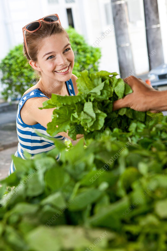 Young woman buying fresh leaves in market