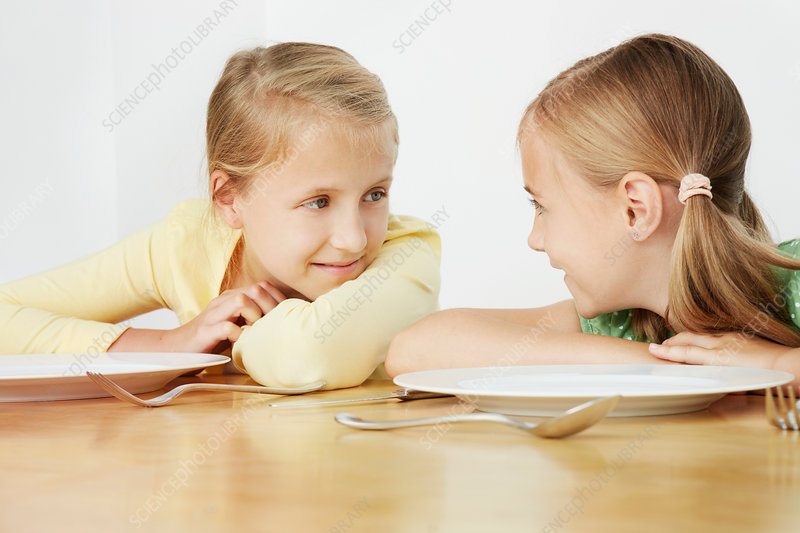 Girls leaning on table with empty plates