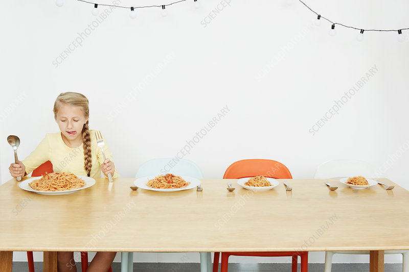 Girl sitting at table with spaghetti
