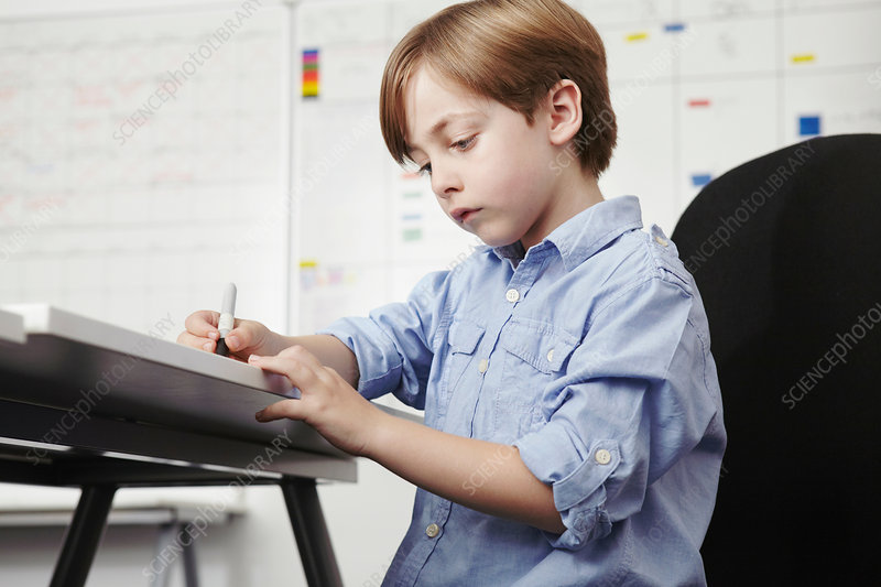 Boy writing at desk in office