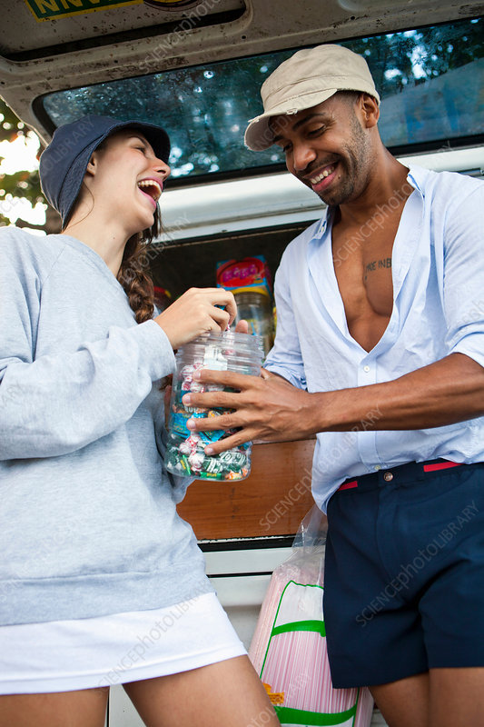 Couple by campervan with candy jar