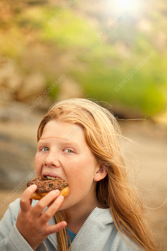 Portrait of teenage girl eating cake