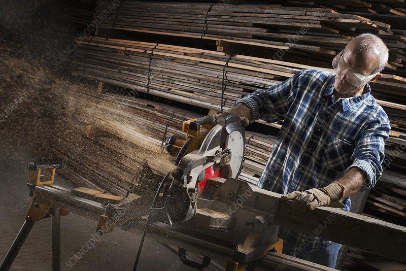 A man in eye goggles using a circular saw